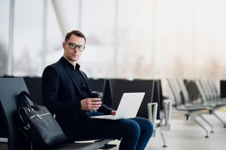 [Młody mężczyzna z laptopem na kolanach, oczekujący na lotnisku na lot  - delayfix.com]